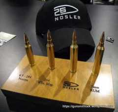 Cartridge for 26 Nosler next to similar cartridges